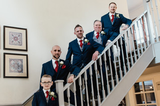 Solihull wedding photographer, the groom & groomsmen posing for a foraml photograph on the stairs at the Westmead Redditch