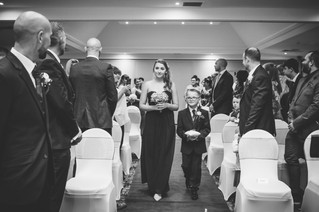 Wedding Photographer Solihull, the bridesmaids walking down the aisle before the bride at the wedding ceremony at Westmead hotel Birmingham & page boy