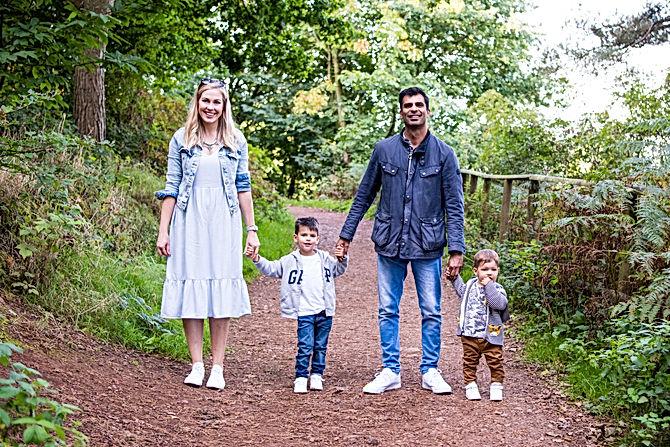 Photographer Birmingham, family photo shoot, family holding hamds walking through the woods