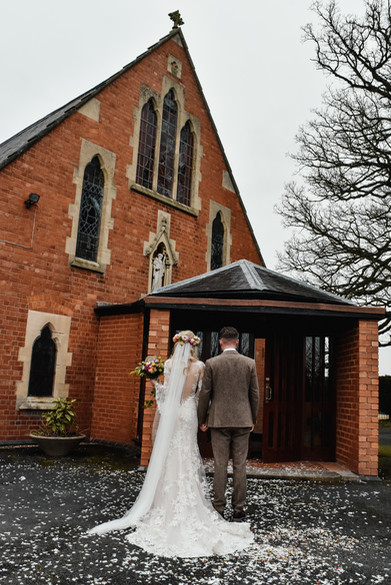 Informal wedding photographer Birmingham, the bride & groom standing with their backs to the camera outside the church they got married in
