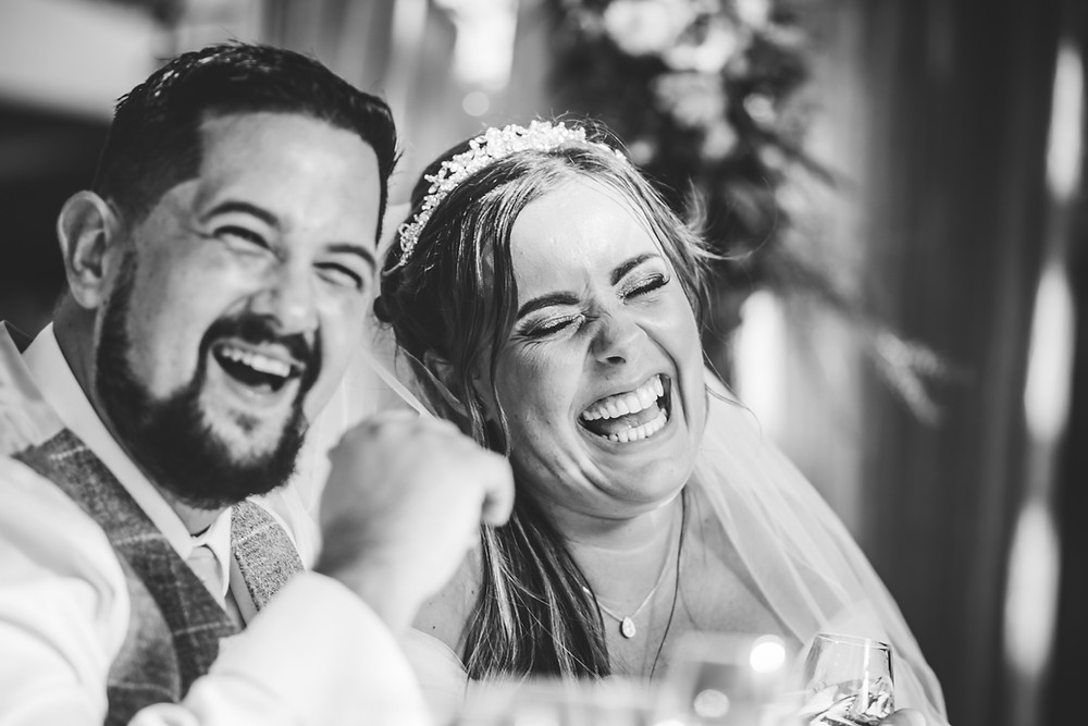Hampton Manor Photographer, Wedding Photographer Birmingham Fun photograph of a bride & groom laughing at a wedding during the speeches