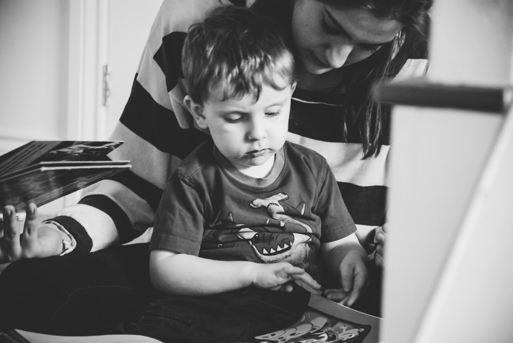 Family Photographer for children with autism, little boy with his carer playing in home photography