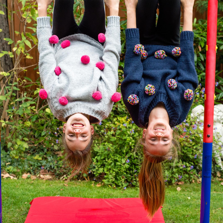 Family Photo shoot Birmingham, two sisters hanging upside down on their gymnastics equipment