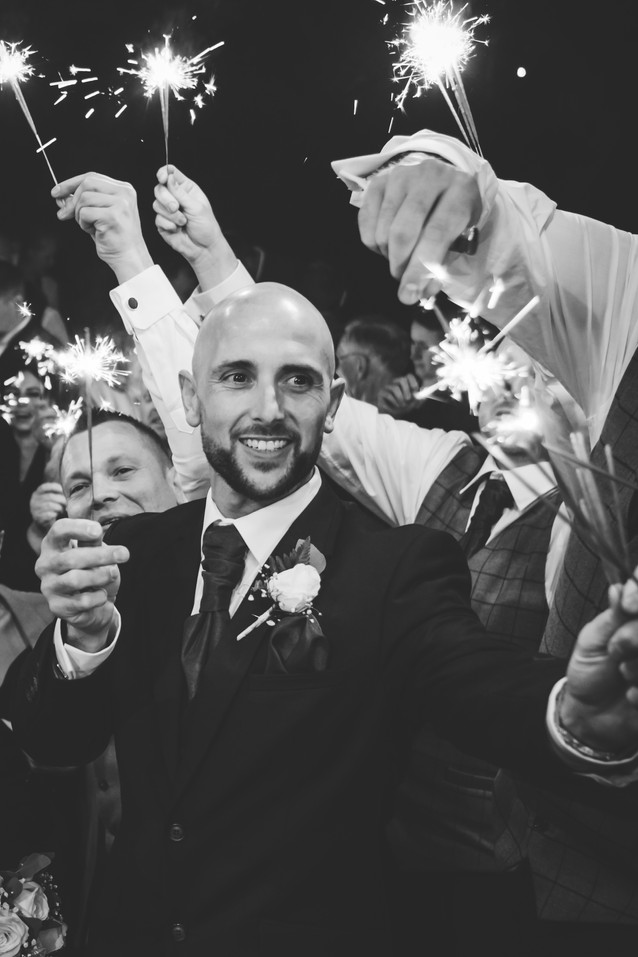 Birmingham Wedding Photographer, Close up image of the groom holding a sparkler at his wedding at Westmead Redditch