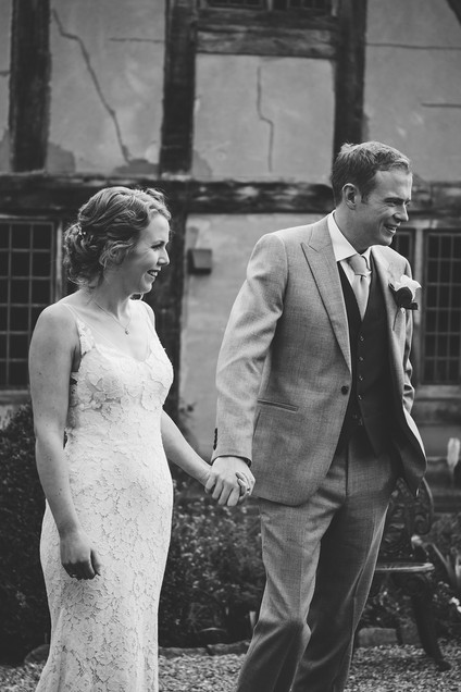 Photography wedding Birmingham, black & white photograph of the bride & groom holding hands after the outdoor wedding ceremony at the lord leycester hospital Warwick wedding venue