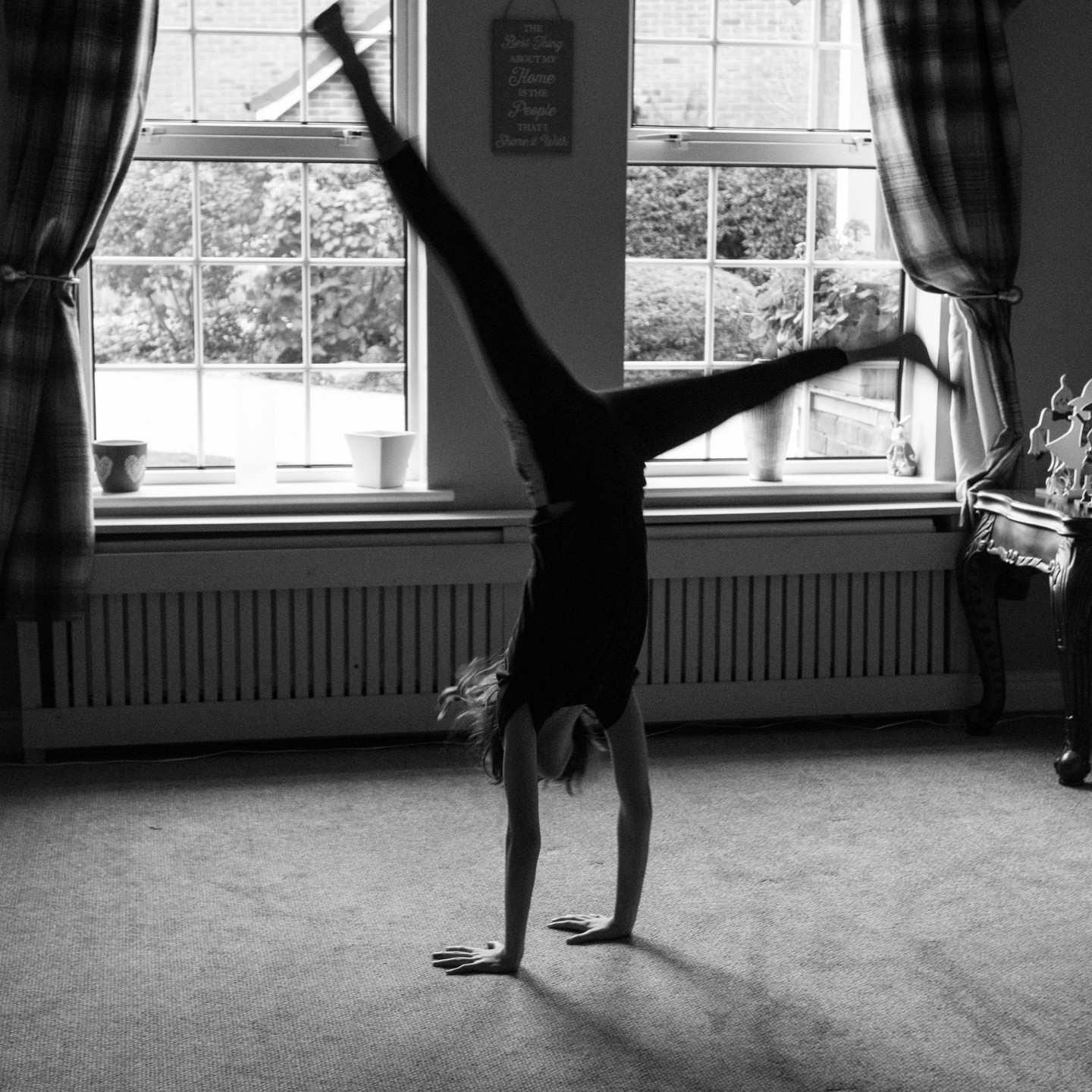 Family Photogrpaher Solihull, young girl doing a handstand in her livingroom