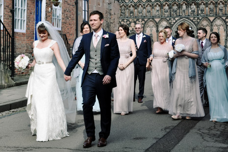 Natural wedding Photographer Solihull, the bride, groom & bridal party walking down the street in lichfield, natural fun image