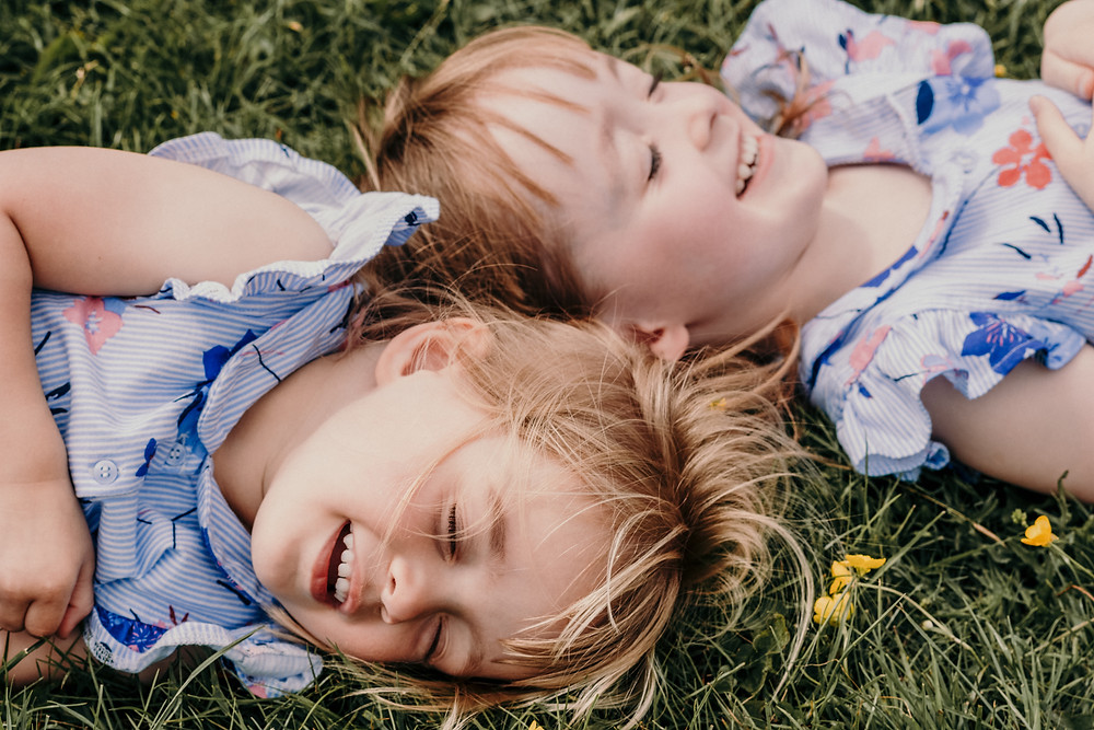 Kids Photographer Birmingham, two sisters lying on the floor outside closing their eyes, fun family photo