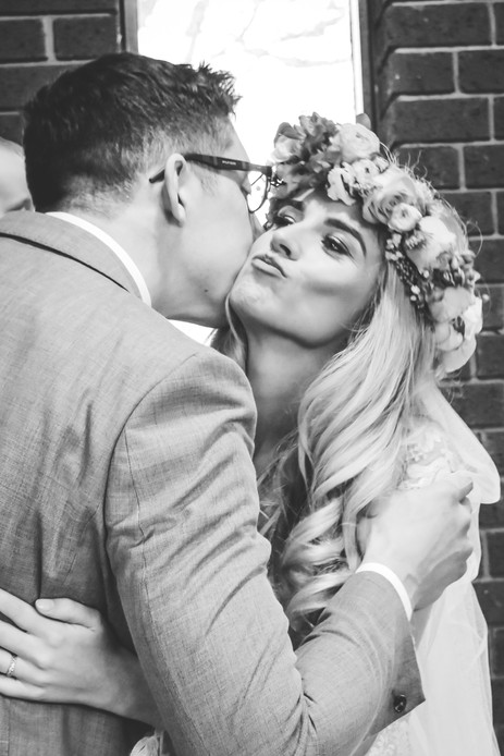 Wedding Photographer Birmingham, the bride kissing one of her guests, black & white natural image