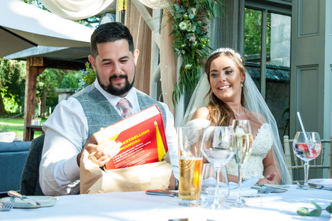 Hampton Manor Wedding photography Birmingham, bride & groom during the speeches sharing a joke