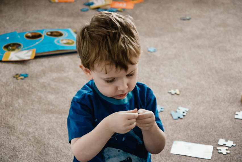 Family Photographer Solihull, lifestyle family Photographer Birmingham, a photo story of a little boy with autism, looking at a jigsaw piece