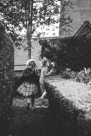 Photographer wedding Birmingham, flower girls running through the maze garden at the lord leycester hospital wedding venue warwick