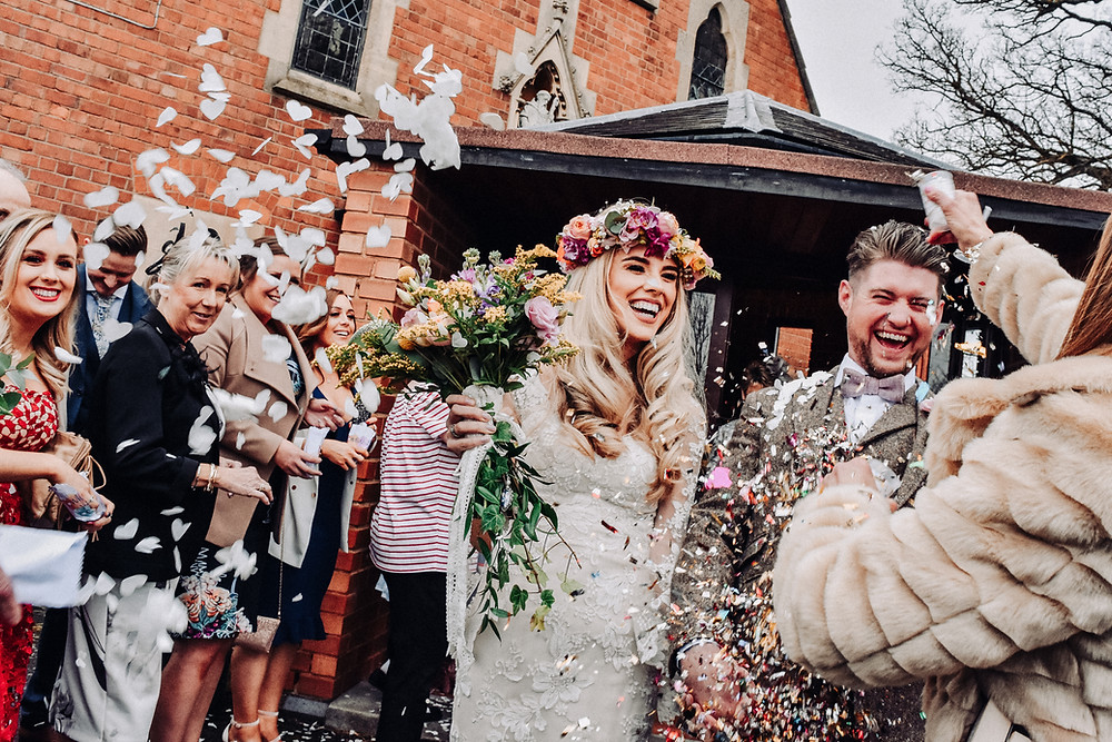 Wedding Photographer Birmingham, young couple having confetti thrown on them after their wedding at Wootton Park Warwickshire