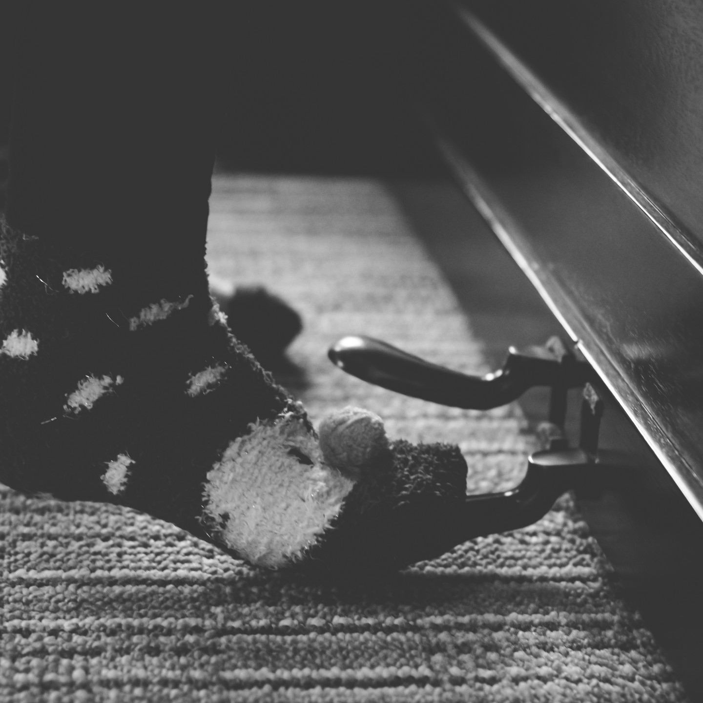 Family Photoshoot Birmingham, close up black & white shot of a young girl playing the piano, detail close up of her foot on the peddle of the piano