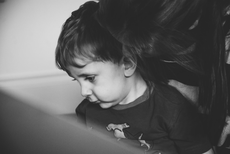 Lifestyle photographer Birmingham, little boy being read to by his carer, black & white Photograph