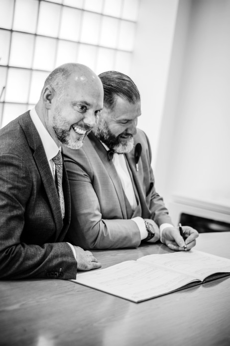 Civil wedding ceremony photographer, Birmingham Wedding Photographer, the grooms signing the register, happy, fun image