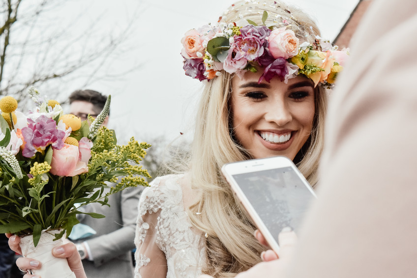 Fun Wedding Photographer Birmingham for non traditional couples, natural close up image of the bride looking at a phone