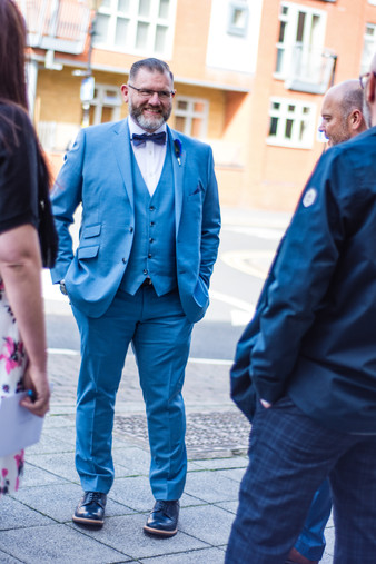 Same sex wedding photographer Birmingham, the groom outside greeting guests, candid informal image