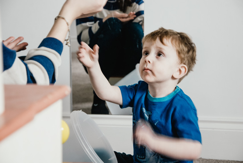 Family Photographer Solihull, little boy with autism looking at his carer playing, photostory
