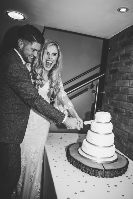 Wedding Photographer Solihull, the bride & groom cutting the cake, fun photograph of the bride & groom at Wootton Park Henley in Arden