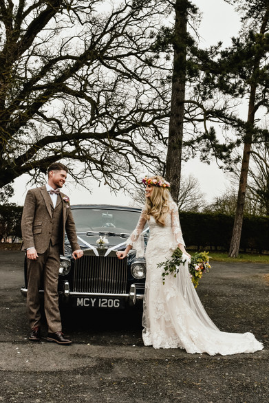 Fun Wedding Photography Birmingham, the bride & groom standing by their vintage wedding car after they got married