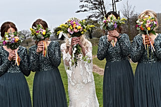 Wedding Photographer Solihull, fun photograph of the bride & bridesmaids holding the wedding bouquets in front of their faces