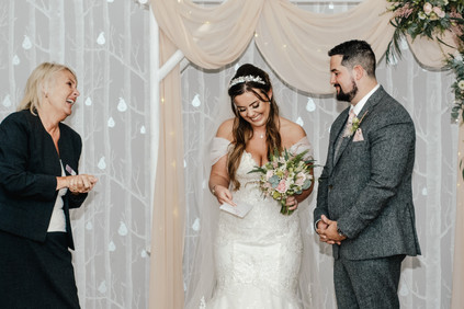 Hampton Manor Photographer Solihull, relaxed, fun photograph of the bride & groom laughing while receiving the marriage certificate