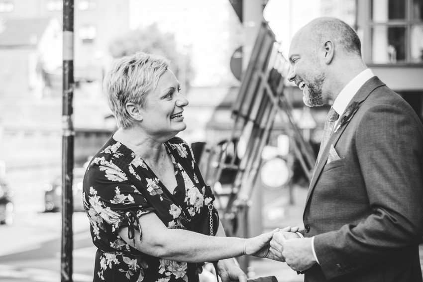 Intimate Wedding Photographer Birmingham, the groom greeting a guest outside Birmingham register office, natural, relaxed photograph