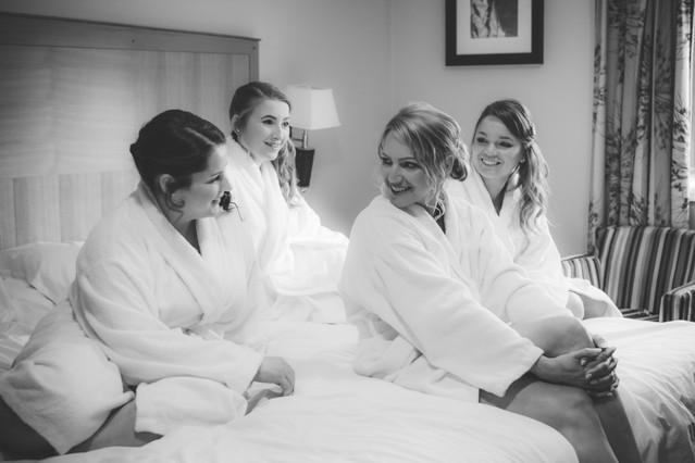 Wedding Photographer Birmingham, elegant wedding, bride & bridesmaids talking on the bed in their robes at the Westmead Birmingham