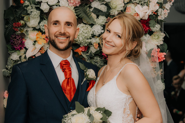 Wedding Photographer Birmingham, the bride & groom portraits standing in front of the floral wall at the Westmead Redditch