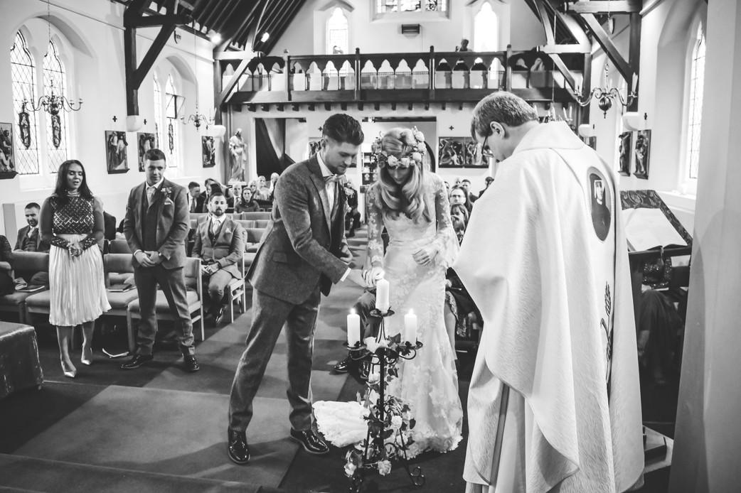 Wedding Photographer Birmingham, full length image of the bride & groom lighting a candle during a catholic wedding ceremony