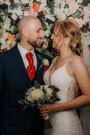Birmingham Wedding Photographer, the bride & groom looking at each other standing in front of the floral display at the Westmead Redditch