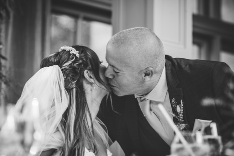 Hampton Manor Wedding Photographer Birmingham, candid photograph of the father of the bride kissing his daughter on the cheek