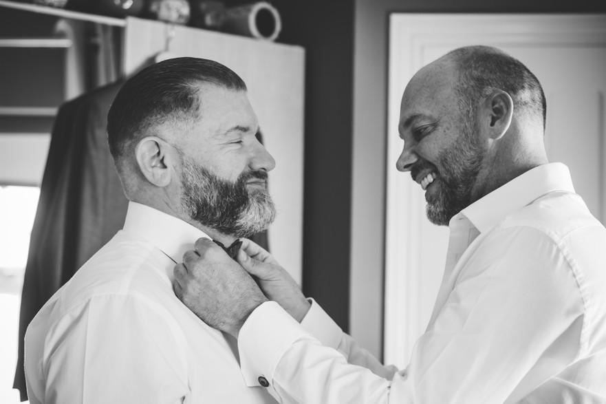 Civil wedding Photographer Birmingham, same sex wedding photographer, the grooms helping each other to get ready, fun, relaxed photograph