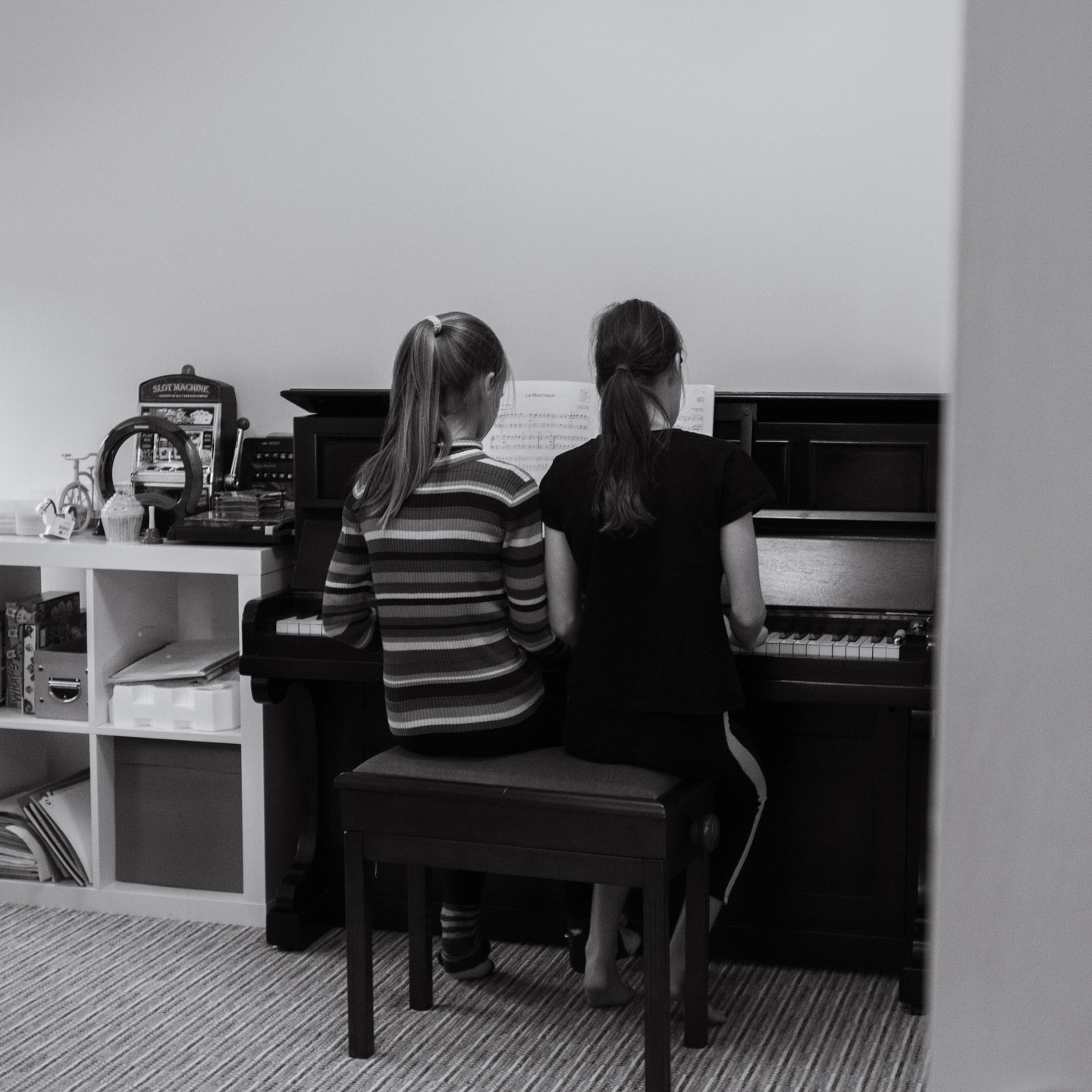 Lifestyle Family photographer Birmingham, two girls playing the piano, candid image