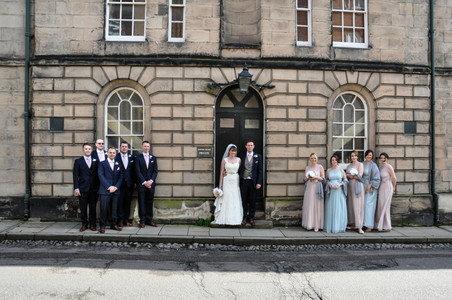 Natural Photographer Birmingham, the bridal party standing outside a building in lichfield