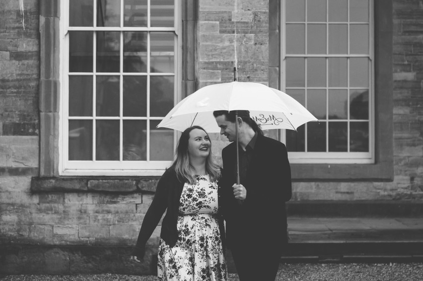 Engagement Photographer Compton Verney Warwickshire, couple looking at eachother laughing under their umbrella black & white photograph