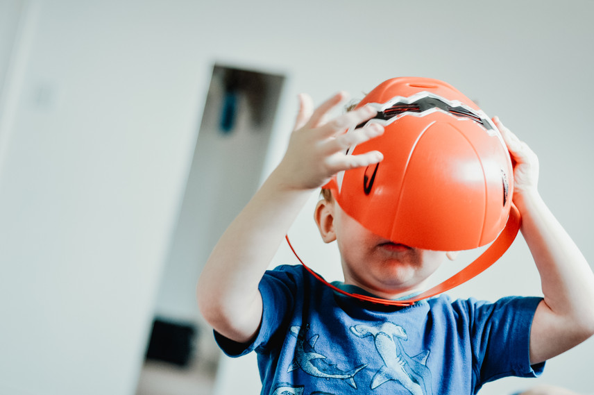 Family Photographer for children with autism, little boy putting an orange helmet on his head,in home photo session
