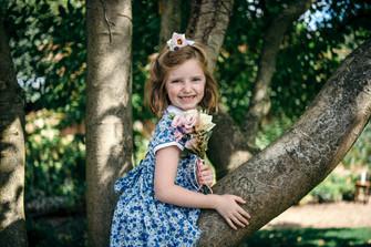 Photographer wedding Birmingham, one of the flower gils sitting in a tree fun portrait, lord leycester hospital wedding venue Warwick