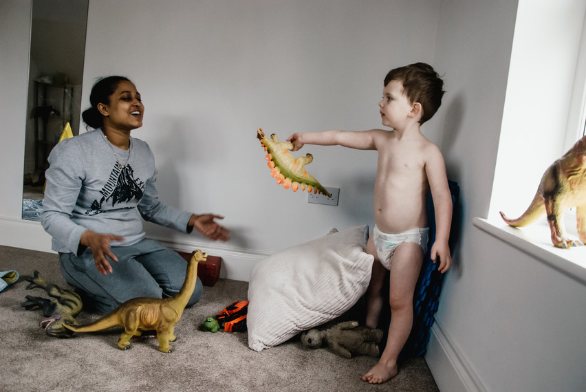 Family Autism Photographer Solihull, little boy playing with his carer & dinosaurs