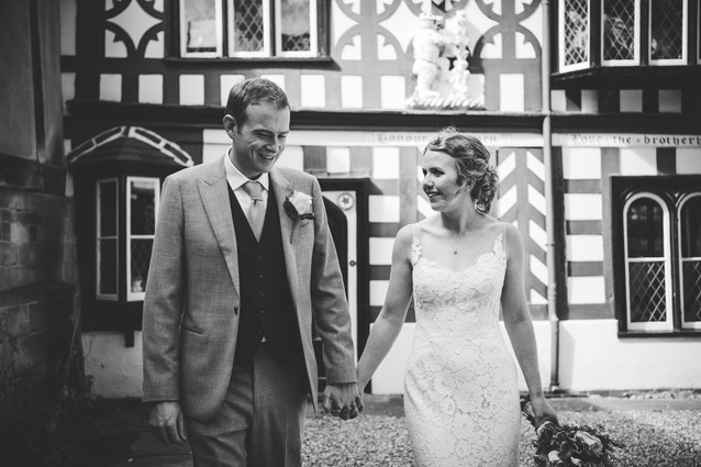 photographer Wedding Solihull, the bried & groom holding hands walking towards the camera ay the lord leycester Warwick wedding