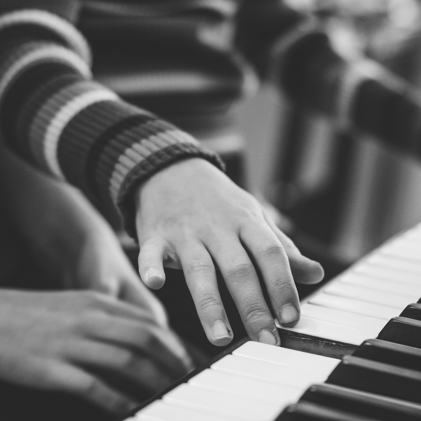 Family Photographer Birmingham, close up image of girls hands on the piano, black & white photo