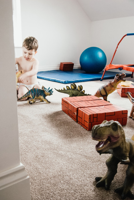 Natural Kids Photography Birmingham, little boy playing with his dinosaur models in the comfort of his own home photo shoot