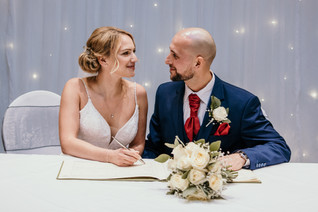 Wedding Photography Birmingham, bride & groom signing the register looking ay each other at the Westmead hotel Birmingham