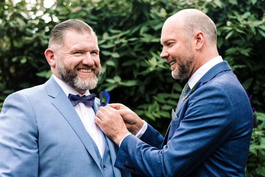 Relaxed wedding photographer Solihull, the grooms helping each other to get ready, buttonholes
