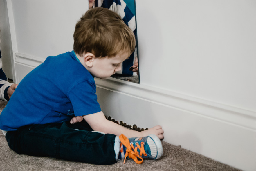 Family Autism Photographer Birmingham, little boy lining up coins against the wall