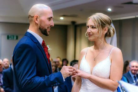 Wedding Photographer Birmingham, bride & groom smiling during the wedding ceremony at the Westmead hotel Birmingham, exchanging rings