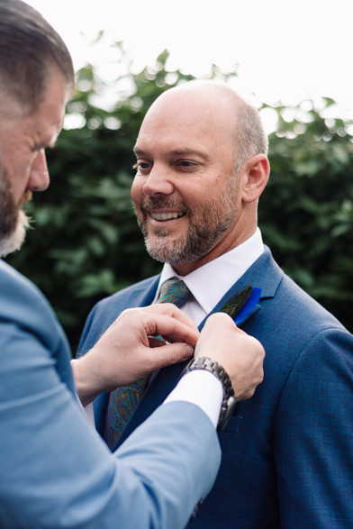 Civil Wedding Photographer Birmingham, the grooms helping each other with the button hole