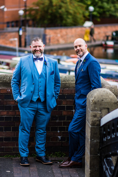 Civil Wedding Photographer Birmingham, the grooms sharing a jke, looking at the camera, full length photograph with Birmingham canals side behind them