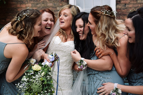 Wedding Photographer Birmingham, the bride & bridesmaids laughing, squashing each other at the west mill derby